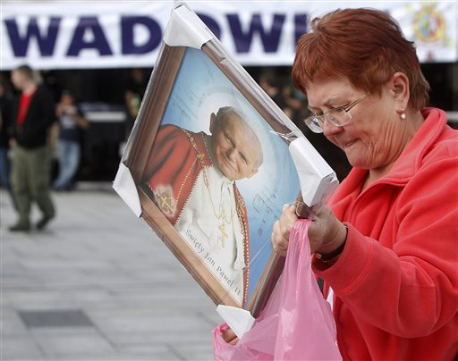A woman places her just-purchased portrait of Pope John Paul II into a carrier bag in the pontiff's hometown of Wadowice, Poland, on Saturday, April 26, 2014, on the eve of Poland's beloved pontiff being made a saint in a Vatican ceremony. Wadowice and nearby Krakow are among the key places linked to John Paul in Poland that are holding observances to mark the occasion. People will be able to see the Vatican ceremony live on giant screens there, and in many other places in Poland. (AP Photo/Czarek Sokolowski)