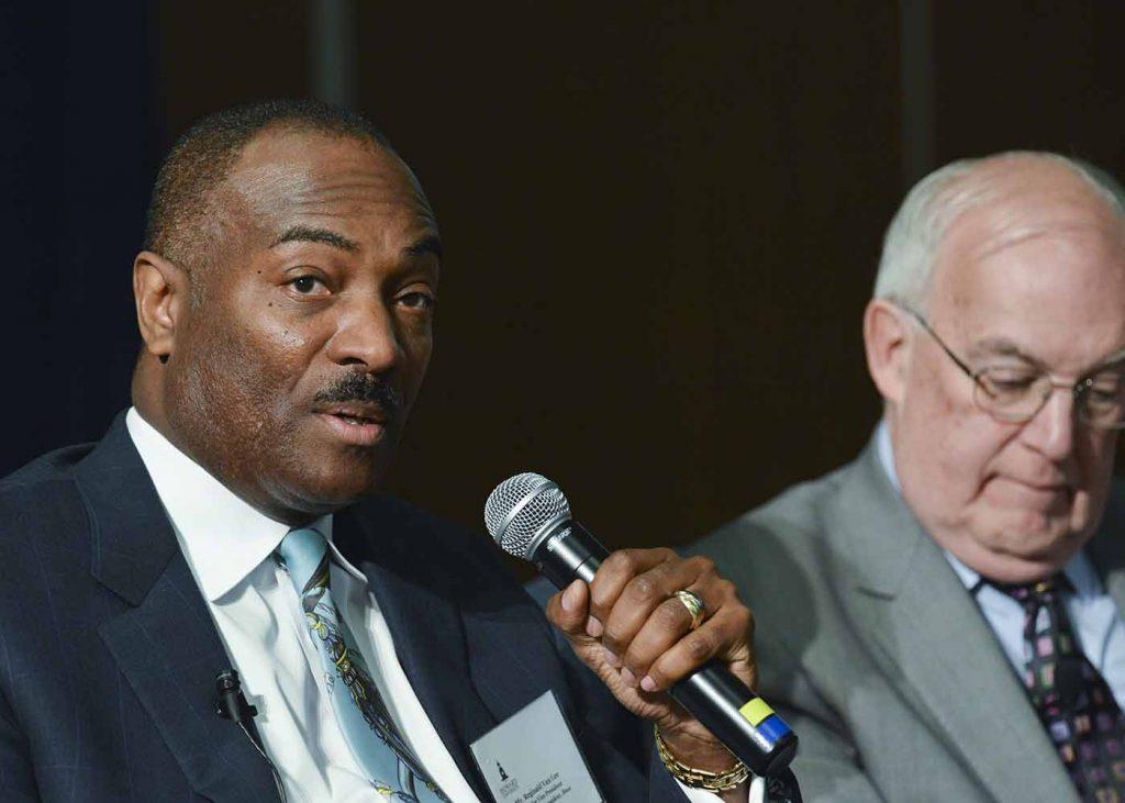 Reginald Van Lee (left), a senior vice president at Booz Allen Hamilton's Washington, D.C. branch, talks about megacommunities at a recent health care symposium at Howard University in Washington, D.C. (Freddie Allen/NNPA)