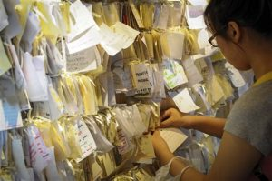 A woman ties a message card for passengers onboard the missing Malaysia Airlines Flight 370 at a shopping mall in Petaling Jaya, near Kuala Lumpur, Malaysia, Thursday, April 10, 2014.(AP Photo)