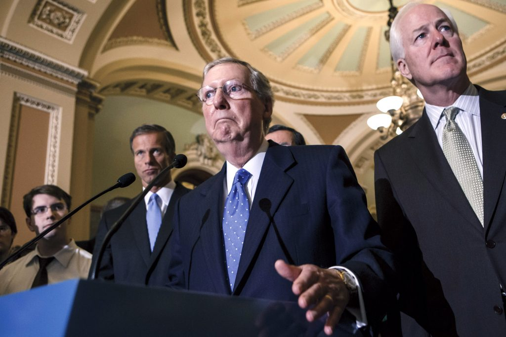Senate Minority Leader Mitch McConnell of Ky., center, accompanied by, from left, Sen. John Thune, R-S.D., Sen. John Barrasso, R-Wyo., and Senate Minority Whip John Cornyn of Texas, speaks with reporters just off the Senate floor on Capitol Hill in Washington, Tuesday, Sept. 24, 2013, as lawmakers struggle with a stopgap spending bill that would prevent a partial government shutdown when the budget year ends next week. Tea party-leaning members of the House GOP caucus successfully attached language to that bill last week that would strip funding for President Barack Obama's health care program. (AP Photo/J. Scott Applewhite)