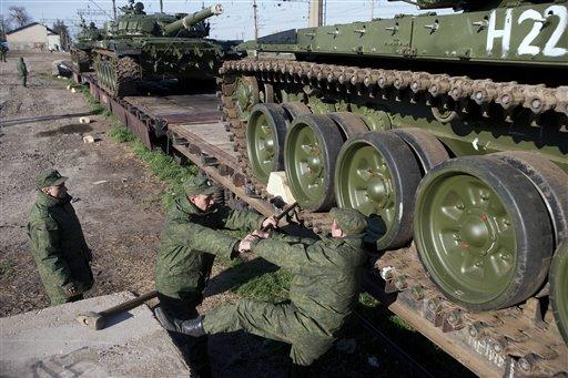 Russian solders prepare to move a Russian tank T-72B at the Ostryakovo railway station not far from Simferopol, Crimea, Monday, March 31, 2014. (AP Photo/Pavel Golovkin)