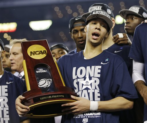 Connecticut guard Shabazz Napier holds the championship trophy after defeating Kentucky 60-54, at the NCAA Final Four tournament college basketball championship game Monday, April 7, 2014, in Arlington, Texas. (AP Photo/David J. Phillip)