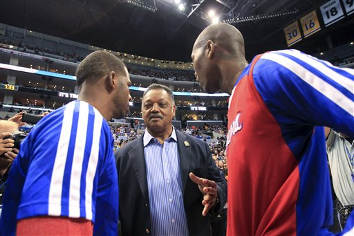 The Rev. Jesse Jackson, center, talks to Los Angeles Clippers' Chris Paul and Jamal Crawford before Game 5 of the Clippers' opening-round NBA basketball playoff series against the Golden State Warriors on Tuesday, April 29, 2014, in Los Angeles. NBA Commissioner Adam Silver announced Tuesday that Clippers owner Donald Sterling has been banned for life by the league. (AP Photo/Ringo H.W. Chiu)