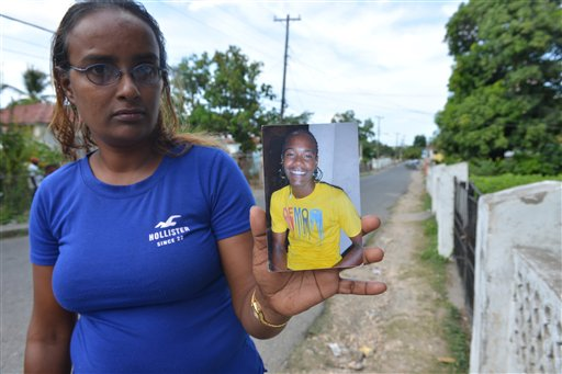 In this photo taken April 17, 2014, in the central Jamaican city of May Pen, Sevina Giderisingh holds a picture of her dead son, Alphanso. The 20-year-old was shot dead by a policeman in a confrontation on the dusty outskirts of this struggling city a few days after graduating from high school. Jamaica's security forces have long been accused of indiscriminate shootings and unlawful killings. But 27 police officers, including eight in May Pen, now face charges of murder brought by an investigative commission probing abuse allegations against Jamaica's security forces. (AP Photo/David McFadden)