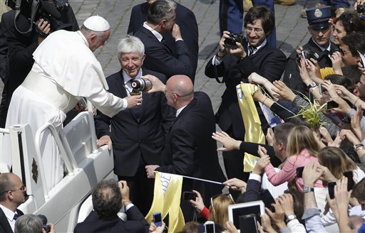 "Vatican police chief commander Domenico Giani, right, pours Pope Francis a drink into a mate gourd, a traditional South American cup, that was offered by faithful as the pontiff is driven through the crowd at the end of a Palm Sunday Mass in St. Peter's Square, at the Vatican, Sunday, April 13, 2014. Pope Francis, marking Palm Sunday in a packed St. Peter's Square, ignored his prepared homily and spoke entirely off-the-cuff in a remarkable departure from practice. Later, he hopped off his popemobile to pose for ""selfies"" with young people in the crowd. In his homily, Francis called on people, himself included, to look into their own hearts to see how they are living their lives. (AP Photo/Gregorio Borgia)"