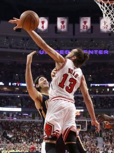 In this March 24, 2014 file photo, Chicago Bulls center Joakim Noah (13) blocks the shot of Indiana Pacers forward Luis Scola during the first half of an NBA basketball game in Chicago. A person familiar with the situation says Bulls center Joakim Noah is the NBA's Defensive Player of the Year. The person spoke Monday, April 21, 2014, on the condition of anonymity because the award had not been announced. (AP Photo/Charles Rex Arbogast, File)