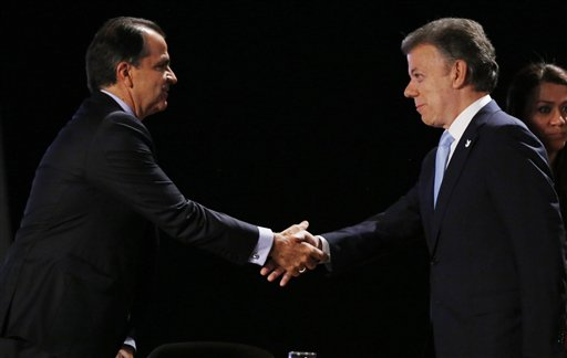 President Juan Manuel Santos, right, who is seeking a second four-year term as candidate for the Social Party of National Unity in the upcoming May 25 presidential election, shakes hands with Oscar Ivan Zuluaga, candidate for the Democratic Center, prior to a televised presidential debate in Bogota, Colombia, Thursday, May 22, 2014. Colombia will hold presidential elections on May 25. (AP Photo/Fernando Vergara)