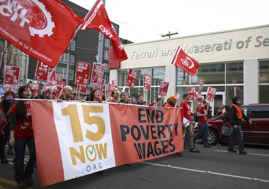 In this March 15, 2014, file photo people march during a rally to raise the minimum wage to $15 per hour in Seattle. Seattle backers the minimum wage hike that would be the highest in the nation, are not slowing down after an election season last fall. (Joshua Trujillo/AP)