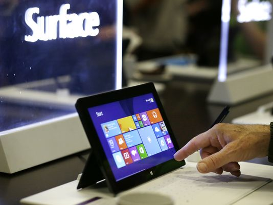 Microsoft shareholders look over Surface tablets on display before the annual shareholder meeting on Nov. 19, 2013, in Bellevue, Wash. (Photo: Elaine Thompson, AP)