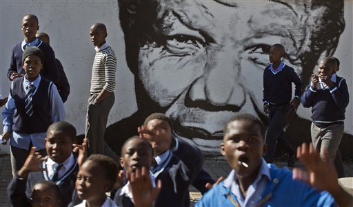 Schoolchildren who had just paid a visit to the former house of the late South African President Nelson Mandela, walk past a mural of Mandela in the Soweto township of Johannesburg, South Africa Friday, May 9, 2014. Vote-counting in elections in South Africa is almost complete, indicating a comfortable win for the ruling African National Congress but also a strengthening of key opposition rivals that promised change after 20 years of leadership by the party that led the fight against apartheid. (AP Photo/Ben Curtis)