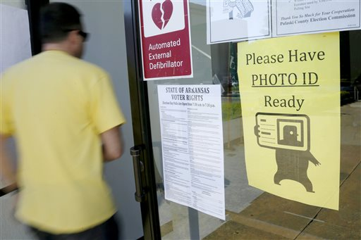 """In this May 5, 2014 file photo, a voter walks past a """"Please Have Photo ID Ready"""" sign as he enters an early-voting polling place in downtown Little Rock, Ark. The Arkansas Supreme Court has tossed out a judge's ruling striking down the state's voter ID law, but stopped short of ruling on the constitutionality of the measure. (AP Photo/Danny Johnston, File)"""