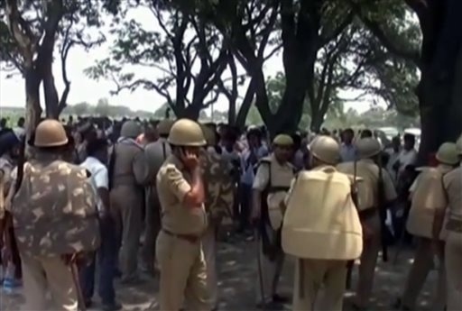 In this Wednesday, May 28, 2014 image taken from video, police stand amongst the crowd near where two teenage sisters were found hanging from a mango tree in the Katra village in Uttar Pradesh state, in northern India. Authorities have arrested three men, including two police officers, suspected of gang-raping and killing the teenagers before hanging their bodies from the tree, sparking renewed public outrage over sexual violence in the country. (AP Photo/NNIS via AP Video)