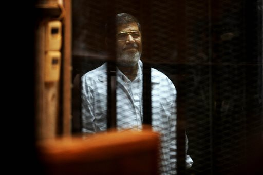 Egypt's ousted President Mohammed Morsi stands inside a glassed-in defendant's cage during his trial on charges related to the prison breaks at the height of the 18-day 2011 uprising against his predecessor Hosni Mubarak in Cairo, Egypt, Wednesday, April 30, 2014. (AP Photo/Ahmed Omar)