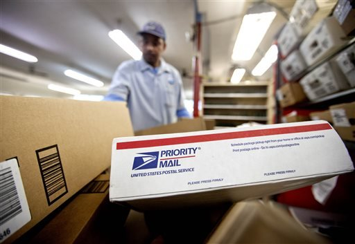 In this Thursday, Feb. 7, 2013, file photo, packages wait to be sorted in a Post Office as U.S. Postal Service letter carrier Michael McDonald, gathers mail to load into his truck before making his delivery run, in Atlanta. The financially struggling U.S. Postal Service said Wednesday, Aug. 14, 2013 it is revamping its priority mail program as part of its efforts to raise revenue and drive new growth in its package delivery business. (AP Photo/David Goldman, File)