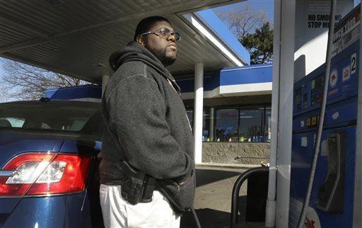 In a photo from April 9, 2014, Greg Champion wears a gun while pumping gas in Detroit. To avoid becoming a carjacking victim, Champion wears a handgun on his hip whenever he's pumping gas. Through May 19, Detroit has recorded 191 carjackings in 2014. (AP Photo/Carlos Osorio)