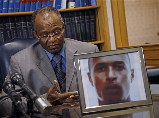 Salvadore Furtado listens during a news conference at his attorney's office in Quincy, Mass., Thursday, May 15, 2014, with a photo of his son, Safiro Furtado. Safiro and Daniel de Abreu were shot to death as they sat in a car in Boston's South End on July 16, 2012. Former New England Patriots' Aaron Hernandez, who already faces a murder charge in a man's shooting death last year, has been indicted Thursday on new murder charges in this 2012 double slaying in Boston. (AP Photo/Elise Amendola)