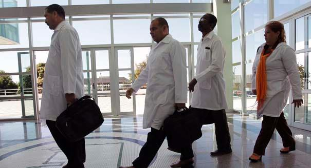 """Cuban doctors arrive for training before being assigned to work in impoverished areas where physicians and medical services are scarce, at the University of Brasilia in Brasilia, Brazil, Monday, Aug. 26, 2013.  Cuban doctors and foreign doctors from other countries are part of the """"More Doctors"""" program to get more physicians working in underserved areas. All will have to spend their first three weeks in the country studying Brazil's public health system and Portuguese. (AP Photo/Eraldo Peres)"""