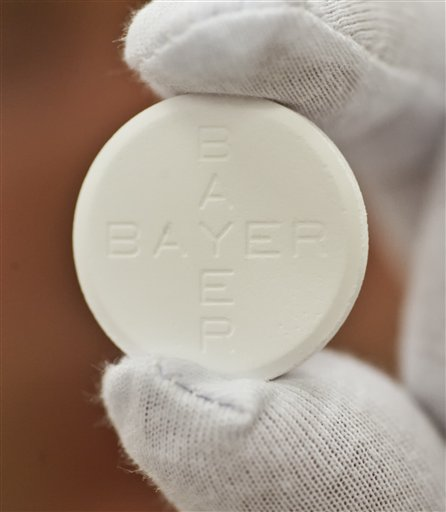 In this photo taken July 6, 2009 worker Roland Ulbrich presents an Aspirin pill made for Italy at the pharmaceutical plant of the Bayer Bitterfeld company in Bitterfeld-Wolfen, eastern Germany.  Germany's Bayer AG says it plans to buy U.S. pharmaceutical company Merck & Co. Inc.'s consumer care business, whose products include the Coppertone suncare range, Claritin allergy medicine and the Dr. Scholl's footcare products, for US$ 14.2 billion. (AP Photo/Eckehard Schulz)