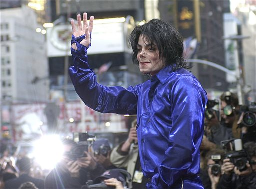 "Nov. 7, 2001 file photo, Michael Jackson waves to crowds gathered to see him at his first ever in-store appearance to celebrate his new album ""Invincible"" in New York's Times Square.When Michael Jackson's record label released his first posthumous album a year after he passed in 2010, producer Rodney Jerkins was asked to work on the project and he declined. Years later, the hitmaker, who worked heavily on Jackson's 2001 comeback album ""Invincible,"" says he now feels comfortable producing Jackson music after the King of Pop suddenly died in 2009. He produced the title track from the upcoming album, ""Xscape,"" out May 13, 2014.  (AP Photo/Suzanne Plunkett, file)"
