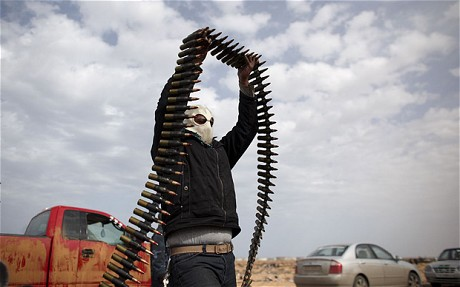 A Libyan volunteer moves ammunition on the outskirts of the eastern town of Ras Lanouf, Libya (AP)