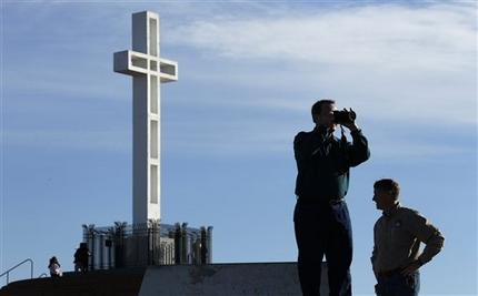 In this Jan. 4, 2011 file photo, Rev. John Fredericksen of Orlando, Fla.,  alongside Burdette Streeter, of San Diego, takes a picture in front of the war memorial cross on Mount Soledad in San Diego. Supporters of the war memorial, which is on public land in San Diego, are planning to ask the Supreme Court to reverse a federal court's decision deeming the cross is unconstitutional. (AP Photo/Gregory Bull, File)
