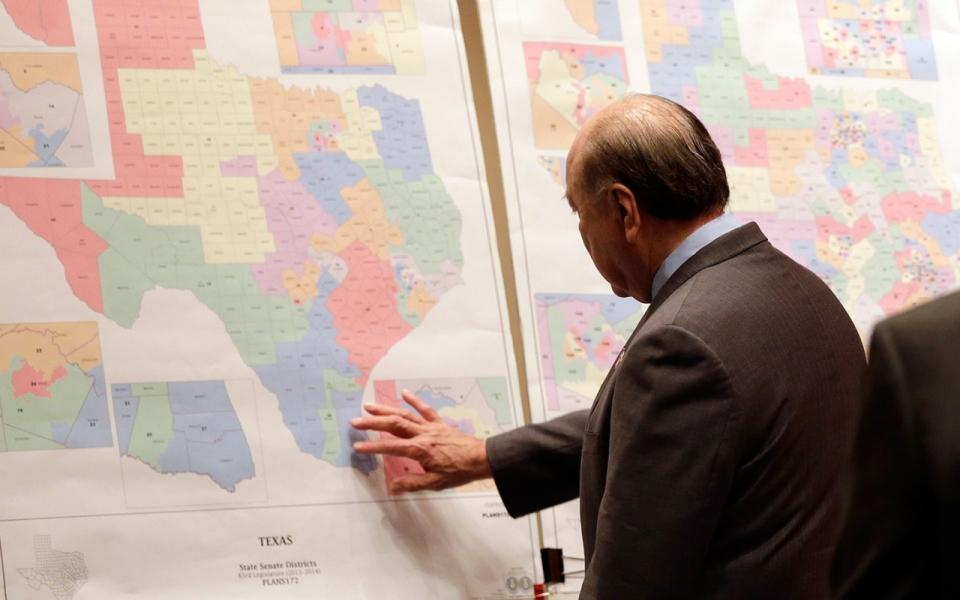 "Texas state Sen. Juan ""Chuy"" Hinojosa looks at maps on display prior to a Senate Redistricting committee hearing, in Austin, Texas. (Eric Gay, File/AP)"