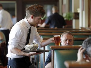 Waiter Spencer Meline serves a customer at Ivar's Acres of Clams restaurant on the Seattle waterfront on May 14, 2014. (AP Photo)