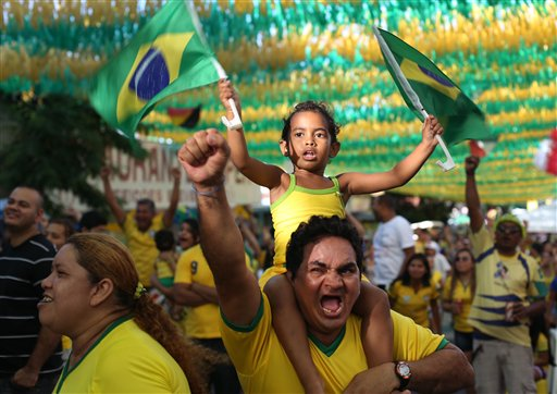 Soccer fans celebrate as they watch on a big screen television, the second goal scored by Brazil's Neymar in the World Cup match against Cameroon, in Manaus, Brazil, Monday, June 23, 2014. Brazil's Neymar scored twice in the first half to lead Brazil to a 4-1 win over Cameroon on Monday, helping the hosts secure a spot in the second round of the soccer World Cup. (AP Photo/Martin Mejia)