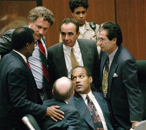 In this Sept. 28, 1995 file photo, O.J. Simpson is surrounded by his Dream Team defense attorneys from left, Johnnie L. Cochran Jr., Peter Neufeld, Robert Shapiro, Robert Kardashian, and Robert Blasier, seated at left, at the close of defense arguments in Los Angeles. (AP PHOTO/SAM MIRCOVICH, POOL, FILE)