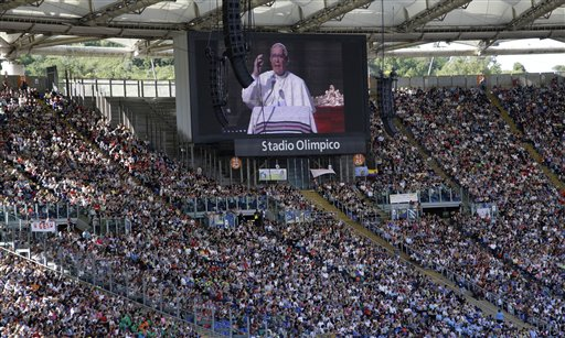 In this photo taken on Sunday, June 1, 2014, the image of Pope Francis is projected on a giant screen during a meeting with faithful at Rome's Olympic stadium. Pope Francis has a message for the World Cup: Let football be a showcase for teamwork and solidarity, not an exhibition of racism and greed. The Argentine-born, football-loving pope recorded a video message that will be broadcast on Brazilian television ahead of Thursday, June 12, 2014 opening match between Brazil and Croatia. In it, Francis said football teaches three lessons that can promote peace and solidarity around the world: the need to train and work hard to reach goals, the importance of fair play and teamwork, and the need to respect and honor opponents. (AP Photo/Gregorio Borgia)