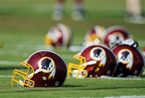 "In this June 17, 2014, file photo, Washington Redskins helmets sit on the field during an NFL football minicamp in Ashburn, Va. The U.S. Patent Office ruled Wednesday, June 18, 2014, that the Washington Redskins nickname is ""disparaging of Native Americans"" and that the team's federal trademarks for the name must be canceled. The ruling comes after a campaign to change the name has gained momentum over the past year. (AP Photo/Nick Wass, File)"