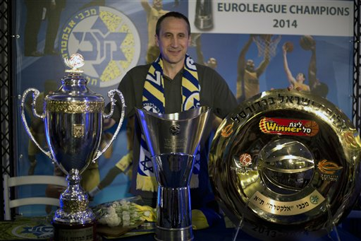 """Maccabi Tel Aviv's head coach David Blatt poses for photographers with the Israeli cup, European club champions cup and the Israeli club champions trophy after a news conference in Tel Aviv, Israel,Thursday, June 12, 2014. David Blatt has stepped down as coach of European club champion Maccabi Tel Aviv to pursue a job in the NBA. Blatt told a news conference on Thursday he wanted to fulfil his """"dream"""" of coaching in the NBA. He says he is weighing offers from unnamed teams. The Cleveland Cavaliers, Minnesota Timberwolves and Golden State Warriors are all believed to be interested. Blatt, who grew up near Boston and played college ball at Princeton, has had a successful career coaching overseas. Last month, he led Maccabi to an upset win over Real Madrid in the European basketball championship. At a championship celebration, Prime Minister Benjamin Netanyahu playfully told Blatt not to leave. (AP Photo/Ariel Schalit)"""