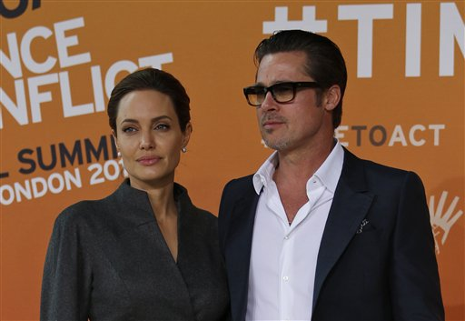 US actress Angelina Jolie, left, Special Envoy of the United Nations High Commissioner for Refugees, accompanied by her partner and US actor Brad Pitt pose for the photographers as they arrive at the 'End Sexual Violence in Conflict' summit in London, Friday, June 13, 2014. The Summit welcomes governments from over 100 countries, over 900 experts, NGOs, Faith leaders, and representatives from international organisations across the world. (AP Photo/Lefteris Pitarakis)