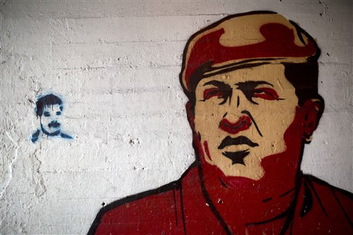 In this Feb. 19, 2014 file photo, a large mural of Venezuela's late President Hugo Chavez, right, is placed next to a small stencil of current President Nicolas Maduro on a wall in downtown Caracas, Venezuela. Charges from old-school leftists that Maduro is mishandling Chavez's legacy have the potential to do real damage. The former bus driver and union leader squeaked out a narrow electoral victory by riding the tide of admiration and mourning that followed Chavez's death from cancer last year. (AP Photo/Rodrigo Abd, File)