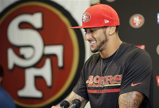 San Francisco 49ers quarterback Colin Kaepernick smiles as he answers question during an NFL football press conference on Wednesday, June 4, 2014, in Santa Clara, Calif. Kaepernick received a new six-year contract extension Wednesday that keeps him with the franchise through the 2020 season. (AP Photo/Marcio Jose Sanchez)