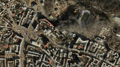 In this file satellite image provided by Skybox Imaging and taken by SkySat-1 on Tuesday, Feb. 18, 2014 at 11:10 a.m. local time, smoke rises from the site of anti-government protests, upper center, in Kiev, Ukraine. Google is buying Skybox Imaging in a deal that could serve as a launching pad for the Internet company to send its own fleet of satellites to take aerial pictures and provide online access to remote areas of the world. (AP Photo/Skybox Imaging, File)