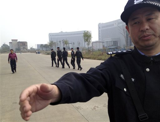 In this Oct. 28, 2013 file photo, a Chinese police officer reaches out towards a journalist outside the courthouse where a trial of Chinese activists from a group that urges fellow citizens to embrace their constitutional rights is underway in Xinyu city in eastern China's Jiangxi province. (AP Photo/Aritz Parra, File)