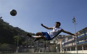 In this June 17, 2014 photo, Andre Rodrigues de Principe, 14, known as Andrezinho to his neighbors, kicks the ball during his practice session in the Vidigal slum of Rio de Janeiro, Brazil. Although he's trained with two of Brazil's premier teams, Fluminense and Vasco da Gama, he's currently only playing for his local squad comprised of other kids from his Vidigal favela, as slums here are known. (AP Photo/Leo Correa)