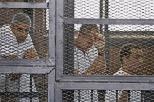 FILE - In this Thursday, May 15, 2014 file photo, from left, Mohammed Fahmy, Canadian-Egyptian acting bureau chief of Al-Jazeera, Australian correspondent Peter Greste, and Egyptian producer Baher Mohamed appear in a defendant's cage along with several other defendants during their trial on terror charges at a courtroom in Cairo. Egyptian Judge Mohamed Nagui Shehata has sentenced the three journalists to seven years in prison Monday, June 23, 2014 in their trial on terrorism-related charges. (AP Photo/Hamada Elrasam, File)