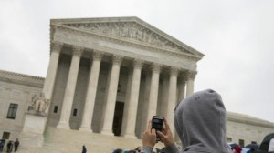 An April file photo shows a Supreme Court visitor using his cellphone . A unanimous Supreme Court said Wednesday that police may not generally search the cellphones of people they arrest without first getting search warrants. (Evan Vucci/AP)