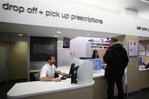 In this Wednesday, May 15, 2013, file photo, a pharmacist works at his desk located next to the prescription pick up counter in New York. New details from two studies reveal more side effects from niacin, a drug that hundreds of thousands of Americans take for cholesterol problems and general heart health.  (AP Photo/Mark Lennihan, File)