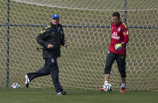 Brazil's coach Luiz Felipe Scolari runs next to goalkeeper Julio Cesar during a practice session at the Granja Comary training center, in Teresopolis, Brazil, Monday, July 7, 2014. Brazil will face Germany on Tuesday in a World Cup semifinal match without Neymar. (AP Photo/Leo Correa)