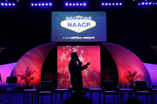A man speaks on a phone on stage after a panel discussion on black turnout for midterm elections and voter suppression during the NAACP annual convention Tuesday, July 22, 2014, in Las Vegas. (AP Photo/John Locher)