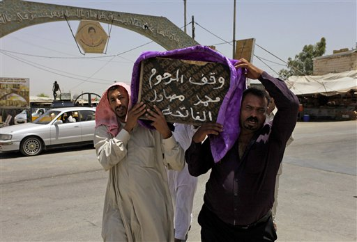 """Mourners carry the coffin of a victim of violence before his burial in the Shiite holy city of Najaf, 100 miles (160 kilometers) south of Baghdad, Iraq, Tuesday, July 1, 2014. Violence has claimed the lives of 2,417 Iraqis in June, making it the deadliest month so far this year, the United Nations said on Tuesday, underlining the daunting challenge the government faces as it struggles to confront Islamic extremists who have seized large swaths of territory in the north and west. Arabic on the coffin reads, """"they stood for the late Mohammed Mosawel."""" (AP Photo/Jaber al-Helo)"""