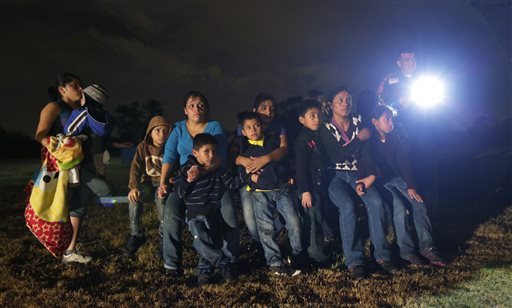 In this June 25, 2014 file photo, a group of immigrants from Honduras and El Salvador who crossed the U.S.-Mexico border illegally are stopped in Granjeno, Texas. Many of the immigrants recently flooding the nation's southern border say they're fleeing violent gangs in Central America. These gangs were a byproduct of U.S. immigration and Cold War policies, specifically growing from the increase in deportations in the 1990s. With weak dysfunctional governments at home, U.S. street gang culture easily took hold and flourished in these countries. (AP Photo/Eric Gay)