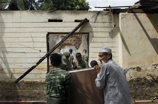 In this Friday, June 27, 2014 photo, a Sri Lankan Muslim man helps army soldiers salvage damaged household items from the debris of a burnt house in Darga Town in Aluthgama about 50 kilometers (31 miles) south of Colombo, Sri Lanka. The onslaught by the Bodu Bala Sena (BBS), a hardline Buddhist group, killed two Muslims in the worst religious violence Sri Lanka has seen in decades. (AP Photo/Eranga Jayawardena)