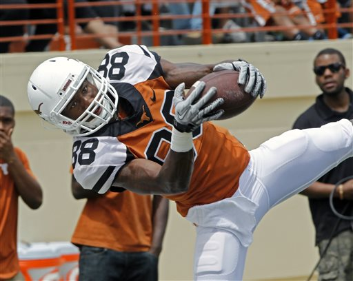 In this April 19, 2014 file photo, University of Texas football player Montrel Meander comes down with a pass during the first half of the Orange and White college football game, in Austin, Texas. A University of Texas police spokeswoman says two Longhorns football players have been charged with felony sexual assault and their arrests are pending. Spokeswoman Cindy Posey says the players charged Thursday, July 24, 2014,  are wide receivers Kendall Sanders and Montrel Meander. (AP Photo/Michael Thomas, File)