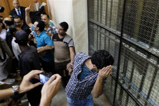 Egyptian men sentenced to life in prison for sexual assaults on women during a number of public rallies in Cairo's iconic Tahrir Square, hide their faces their trial at a court in Cairo, Egypt, Wednesday, July 16, 2014. The court sentenced many men to prison for sexual violence following the government's decision to toughen penalties. Sexual violence has been on the rise in Egypt, particularly during public gatherings in the past three years. (AP Photo/Aly Hazzaa, El Shorouk) EGYPT OUT