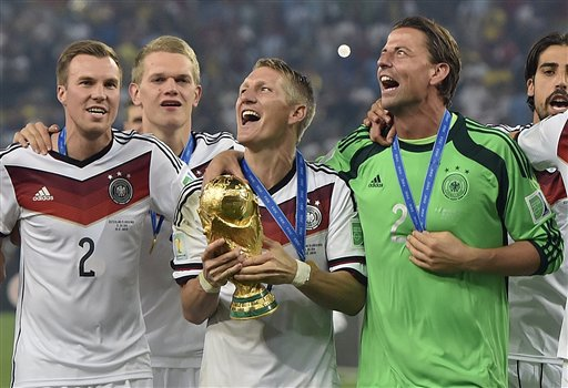 Germany's Bastian Schweinsteiger celebrates with the trophy after the World Cup final soccer match between Germany and Argentina at the Maracana Stadium in Rio de Janeiro, Brazil, Sunday, July 13, 2014. Germany won the match 1-0.   (AP Photo/Martin Meissner)