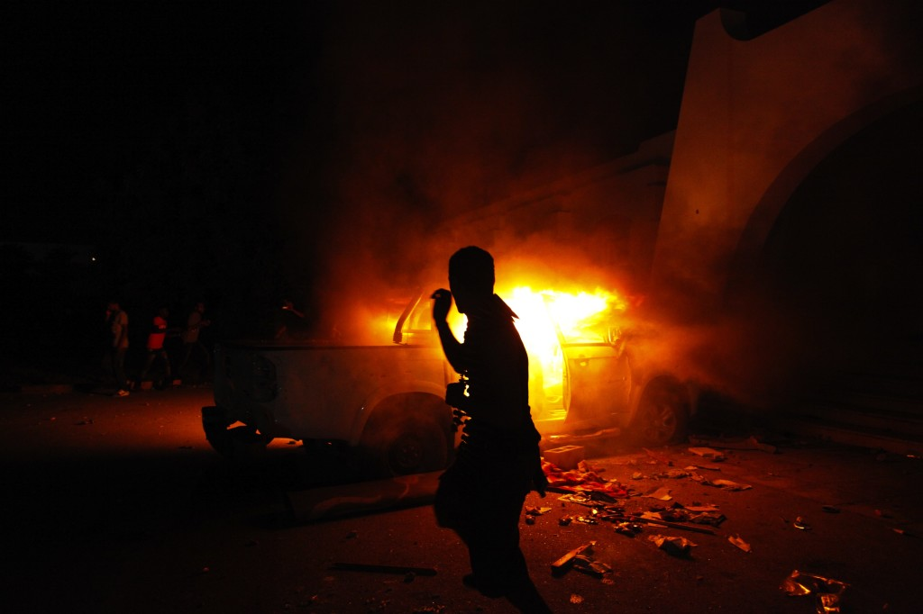A Libyan civilian watches one of Ansar al-Shariah Brigades cars on fire, after hundreds of Libyans, Libyan Military, and Police raided the Brigades base, in Benghazi, Libya, Friday, Sept. 21, 2012. (AP Photo/Mohammad Hannon)